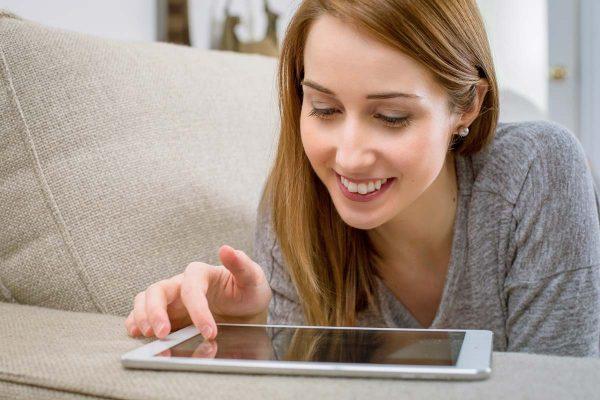 Frau liegt auf Sofa und plant neues Bad mit 3D Badplaner auf Tablet